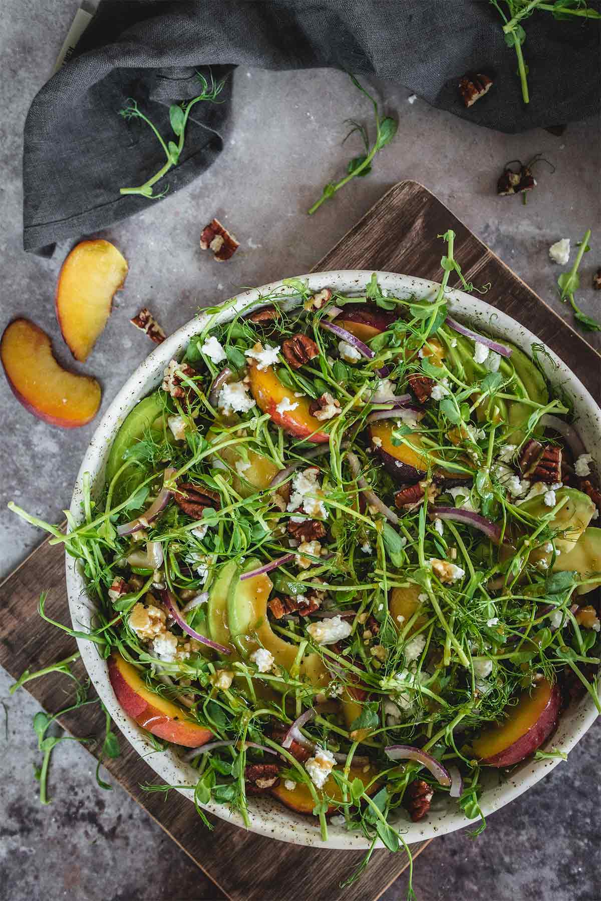 Healthy microgreen salad with peaches and avocado served in a plate