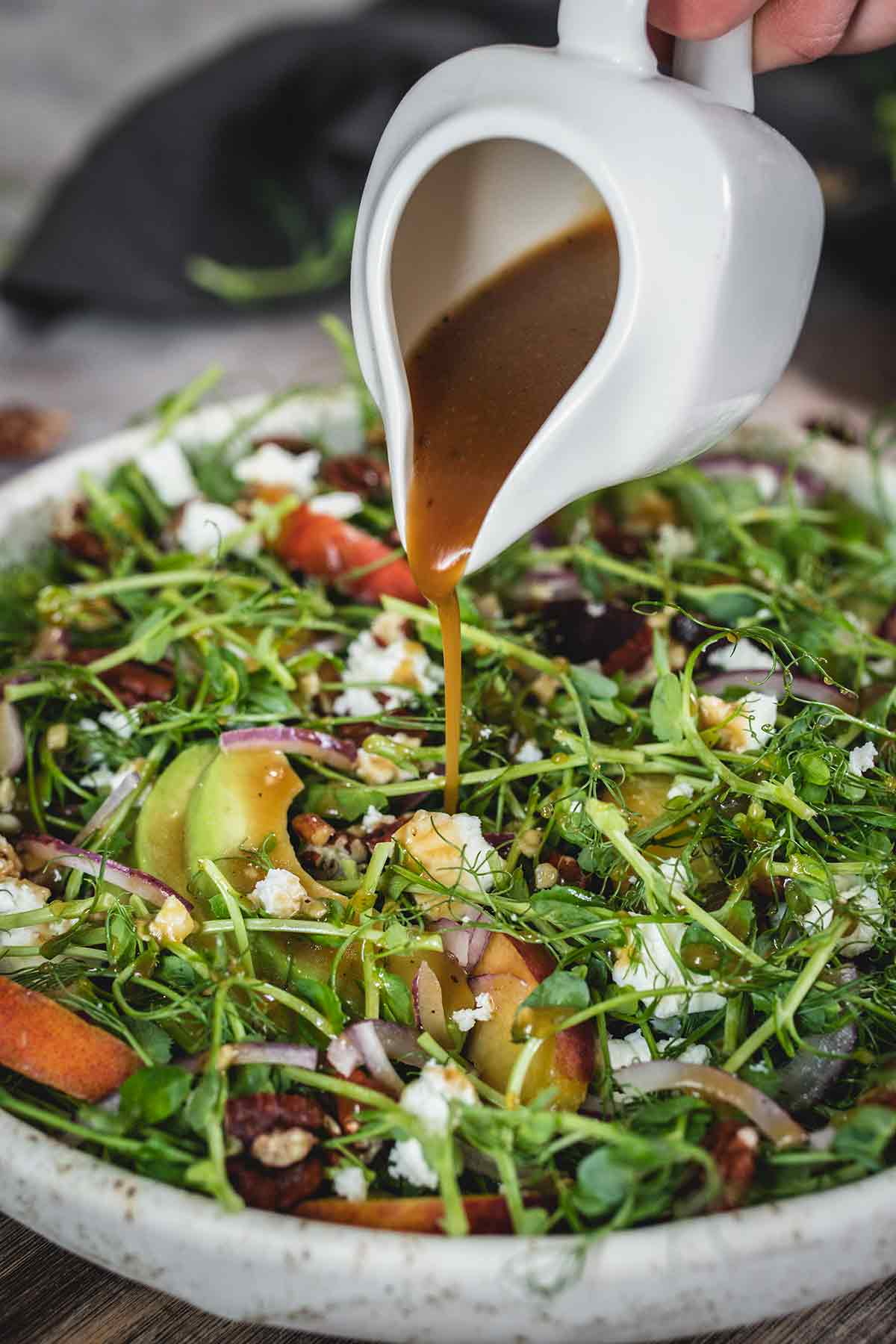 Pouring dressing over salad made with peaches, avocado and microgreens